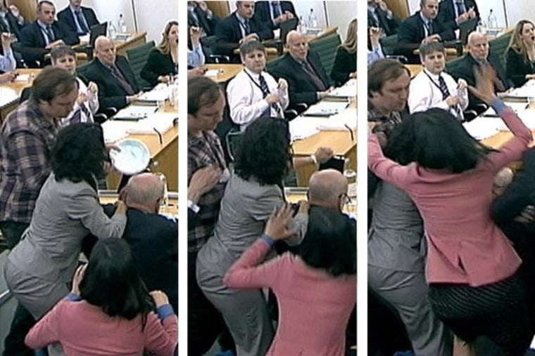 Wendi Murdoch (in the pink suit) lunges towards a man trying to attack her husband during a meeting with British Parliament in London on Tuesday.