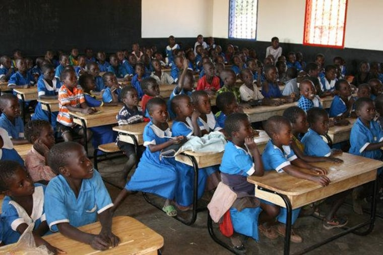 Kids enjoying their new desks post-K.I.N.D. delivery in Malawi.