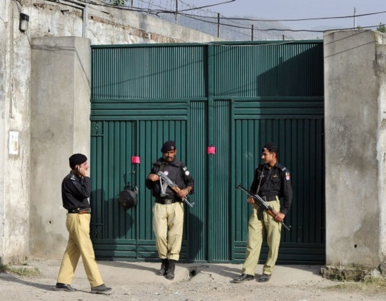 Pakistani police stand guard at the sealed main gate to bin Laden's compound (May 4 - Abbottabad, Pakistan)
