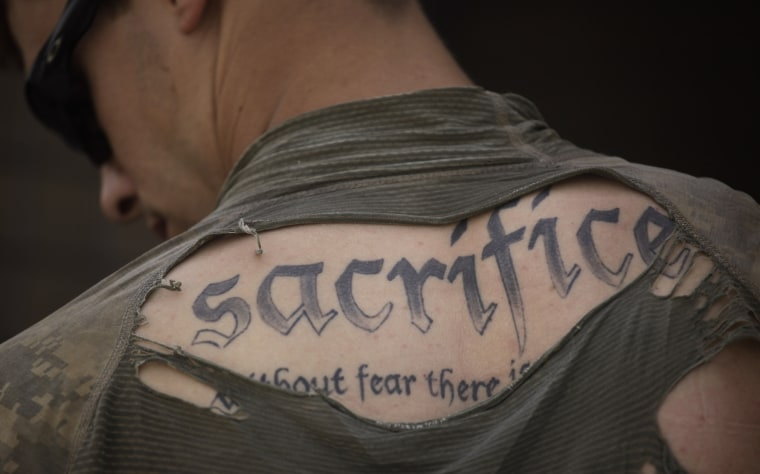 FILE - In this May 8, 2010 file photo, a tattoo on the back of U.S. Army Sgt. James Wilkes of Rochester, N.Y., is seen through his torn shirt after a foot patrol with 1st Platoon, Charlie Company, 2nd Battalion, 1st Infantry Regiment, of the 5th Styker...