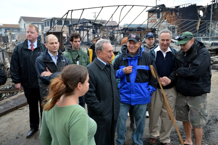 New York City Mayor Michael Bloomberg (C) and US Senator Charles Schumer (2nd R) view damage in the Breezy Point area of Queens in New York on October 30, 2012 after fire destroyed about 80 homes as a result of Hurricane Sandy which hit the area on...