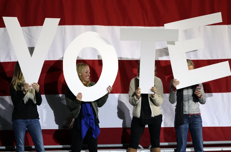 """Women hold up signs spelling """"vote"""" on a stage being prepared for a speech by President Barack Obama at a campaign rally at the Community College of Aurora, in Denver, Sunday, Nov. 4, 2012. (AP Photo/Brennan Linsley)"""