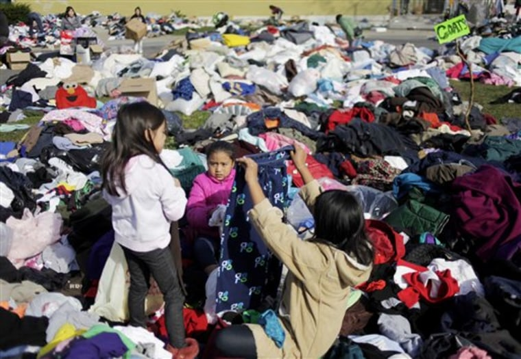 Jasmine Vargas, center, looks through donated clothes at an aid station in the Midland Beach section of Staten Island, New York, Monday, Nov. 5, 2012.  The massive storm that started out as Hurricane Sandy slammed into the East Coast and morphed into a...