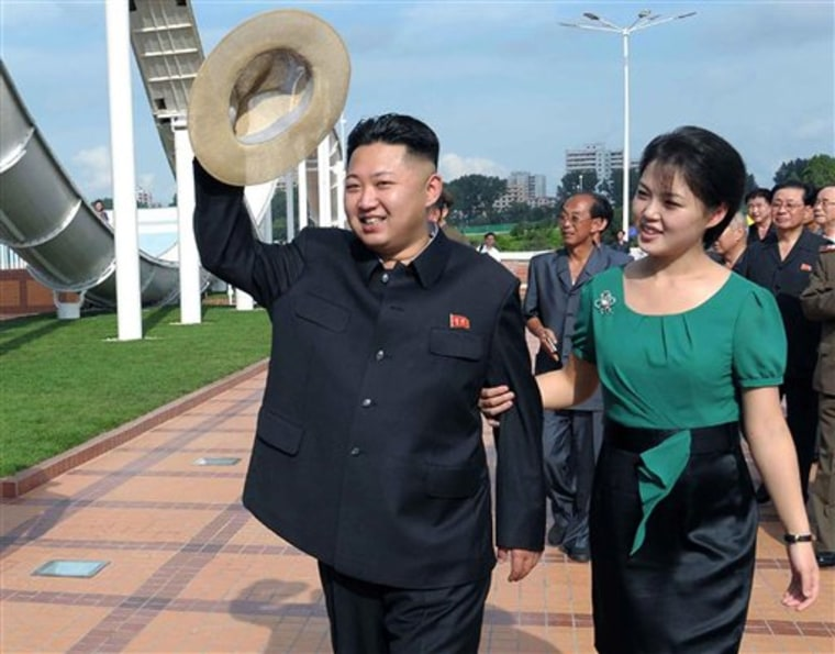 FILE - In this July 25, 2012 file photo released by the Korean Central News Agency and distributed in Tokyo by the Korea News Service, North Korean leader Kim Jong Un, accompanied by his wife Ri Sol Ju, waves to the crowd as they inspect the Rungna...