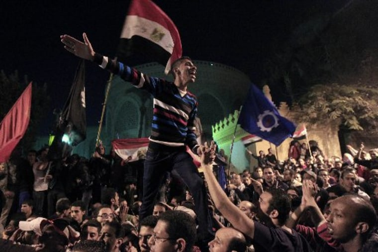 Protesters against Egypt's President Mohamed Mursi celebrate after peacefully breaking past barbed wire barricades guarding the presidential palace in Cairo December 7, 2012. Tens of thousands of Egyptian protesters surged around the presidential...