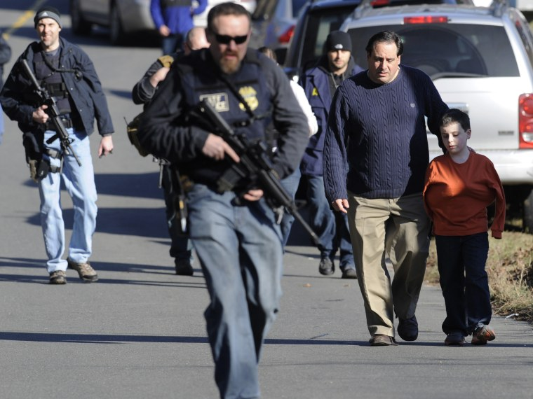 Parents leave a staging area after being reunited with their children following a shooting at the Sandy Hook Elementary School in Newtown, Conn., about 60 miles (96 kilometers) northeast of New York City, Friday, Dec. 14, 2012. (Photo by: Jessica Hill...