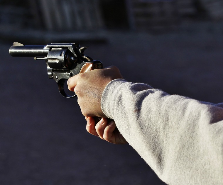 A man shoots a revolver, at Dragonman's firing range and gun dealer, outside Colorado Springs, Colo., Sunday Dec. 23, 2012. (Photo by Brennan Linsley/AP)