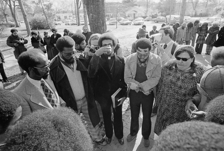 Members of the Wilmington 10 hold a brief communion service before boarding a prison bus on Feb. 2, 1976 in Burgaw, North Carolina, as they surrendered to start prison terms on convictions growing out of 1971 racial disorders in Wilmington, N.C. (AP...