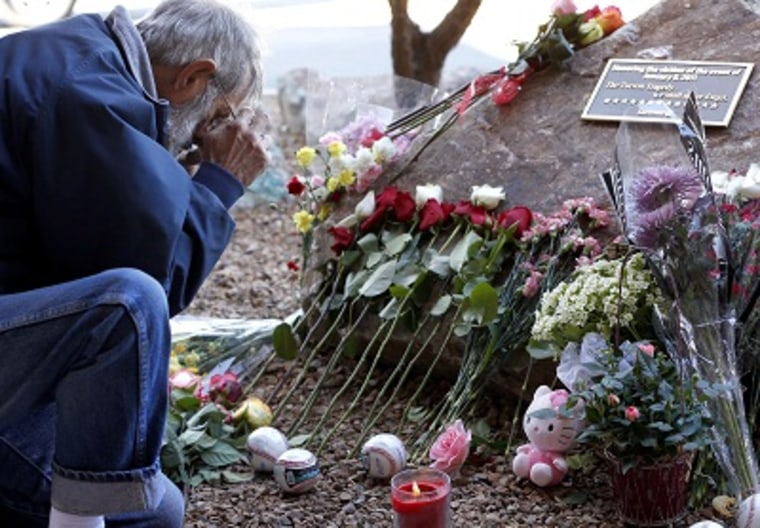 Nick Leo visits a memorial for shooting victims on Tuesday, Jan. 8, 2013 outside the Safeway supermarket where a gunman shot former Rep. Gabrielle Giffords and killed six people. (Photo by Matt York/AP Photo)