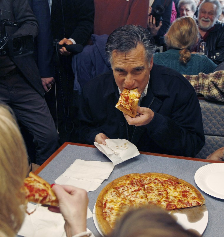 Republican presidential candidate former Mass. Gov. Mitt Romney takes a bite of pizza during lunch with his wife Ann while campaigning at Village Pizza in Newport, N.H., Wednesday Dec. 20, 2011. (AP Photo/Charles Krupa)