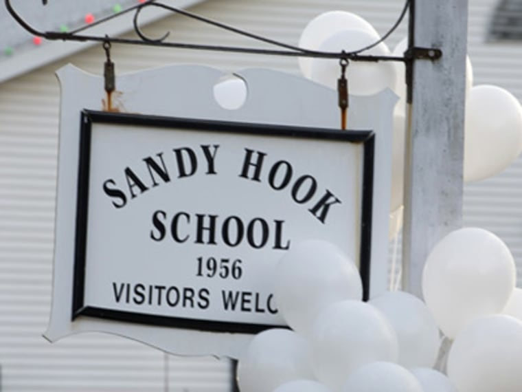 Balloons hang on a sign at the entrance to Sandy Hook School in Newtown, one day after a gunman killed 20 students and six educators. (File photo by Don Emmert/Getty Images)