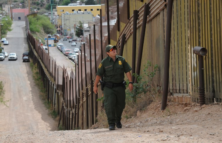 A U.S. Border Patrol officers walks beside the border fence that divides the US from Mexico in the town of Nogales, Arizona. (Photo by Mark Ralston/AFP/Getty)