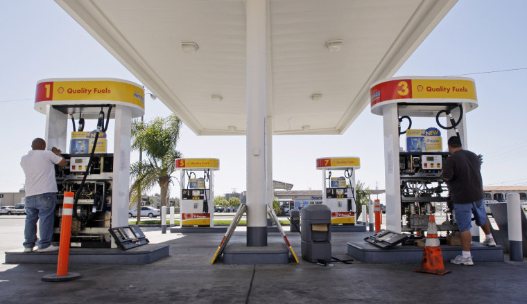 David Berri, right, and his assistant Adolfo Mendez install new valves and electronic controls to a pair of gas pumps at the Shell station Berri owns in Santa Ana, Calif., Saturday, March 28, 2009.  (AP Photo/Reed Saxon)