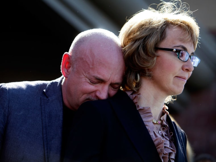 Mark Kelly leans his head on the shoulder of his wife and former congresswoman Gabby Giffords at a in Tucson, Arizona on March 6, 2013. (Photo by Joshua Lott/Getty Images)