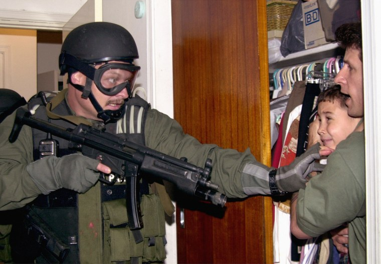 In this fourth of seven sequential photos, Elian Gonzalez is held in a closet by Donato Dalrymple, right, as government officials search the home of Lazaro Gonzalez for the young boy, early Saturday morning, April 22, 2000, in Miami. (AP Photo/Alan Diaz)