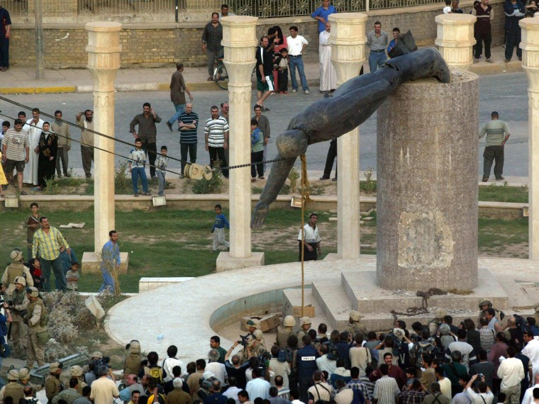 Iraqis watching a statue of Iraqi President Saddam Hussein as it is pulled down in Baghdad's al-Fardous square on April 9, 2003. (Photo by Patrick Baz/AFP/Getty Images, File)