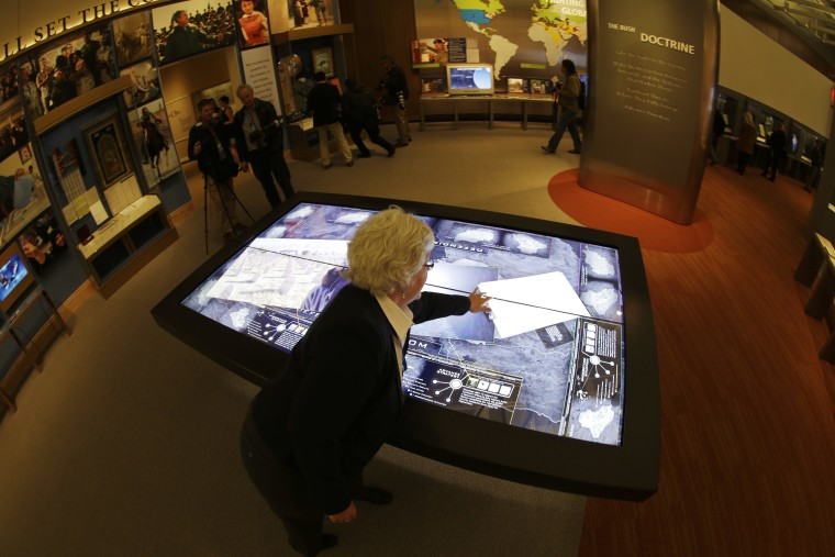 Docent Patricia Flynn demonstrates an interactive with information about conflicts in Afghanistan and Iraq during a tour of the George W. Bush Presidential Center Wednesday, April 24, 2013, in Dallas. More than 8,000 people are expected to attend the...