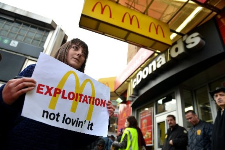 A woman carries a sign past a McDonald's on East 125th Street and Lexington Avenue in Harlem during a protest by fast food workers and supporters for higher wages April 4, 2013 in New York. (STAN HONDA/AFP/Getty Images)