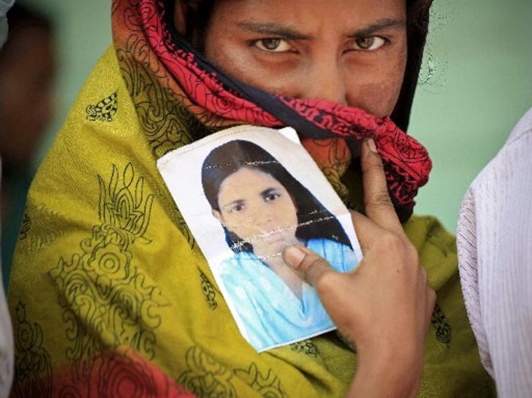 A woman holds a photo of her missing sister after a garment factory building collapsed last week in Savar near Dhaka, Bangladesh, Friday May 3, 2013. (AP Photo/Ismail Ferdous)