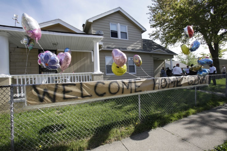 """A """"Welcome Home Gina """" sign hangs on a fence outside the home of Gina DeJesus  Tuesday, May 7, 2013, in Cleveland.  DeJesus, Amanda Berry and Michelle Knight, who went missing separately about a decade ago, were found in a home just south of downtown..."""