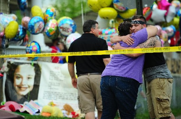 Friends and relatives stand in front of the family house of Gina DeJesus, one of the three women which were held captive for a decade, as it stands decorated by well wishers May 7, 2013 in Cleveland, Ohio. Three brothers have been arrested in...