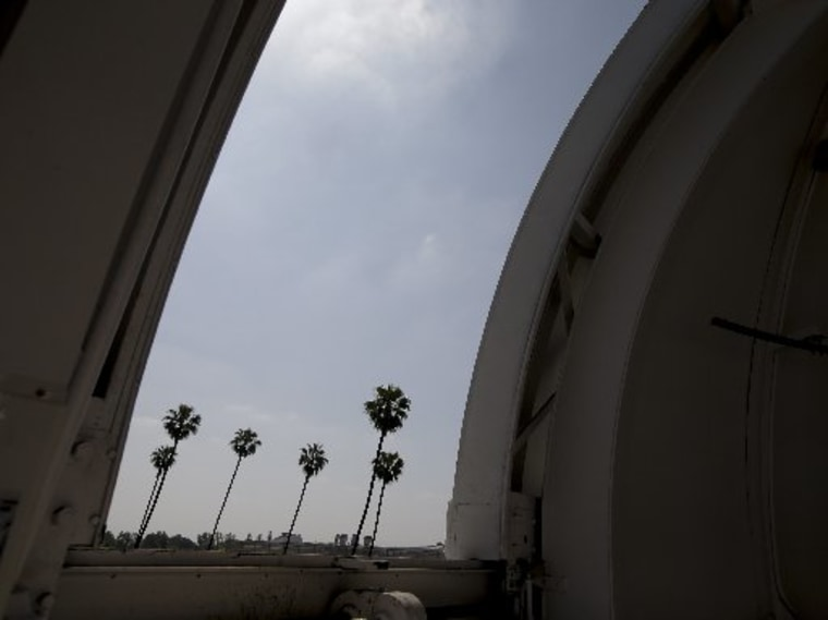 Palm trees are seen through an observatory door at Caltech's Linde + Robinson Laboratory in Pasadena, Calif., Friday, April 12, 2013. A mile above this city, sensors gaze down on the basin from atop Mount Wilson the way a satellite fixates on Earth,...