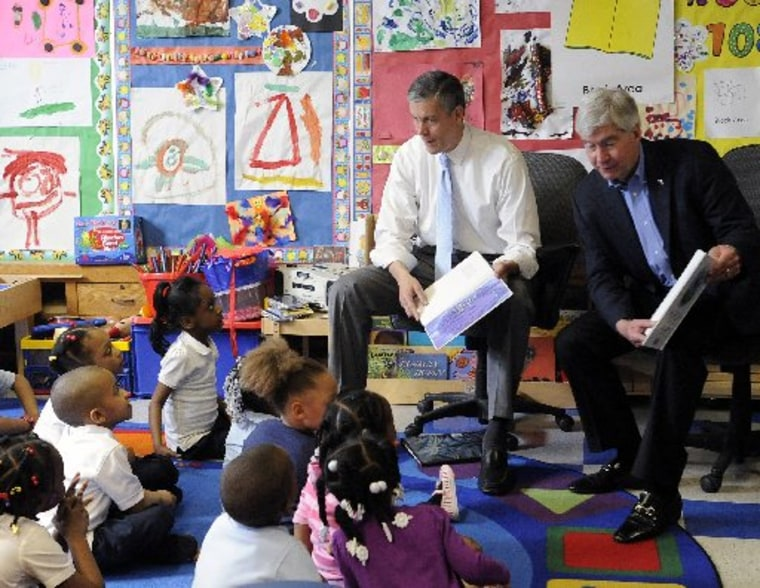 """U.S. Education Secretary Arne Duncan and Michigan Gov. Rick Snyder read """"The Rainbow Fish"""" book to a pre-kindergarten class at Thirkell Elementary School in Detroit on Monday, May 6, 2013.  (AP Photo/Detroit News, David Coates)"""
