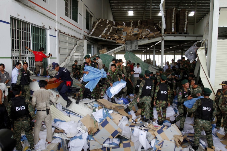 Rescue workers and soldiers search through a site of the accident in a shoe factory in the Kong Pisei district of Kampong Speu province, 50 km (30 miles) west of the capital, Phnom Penh May 16, 2013. Three people were killed when the ceiling of a...