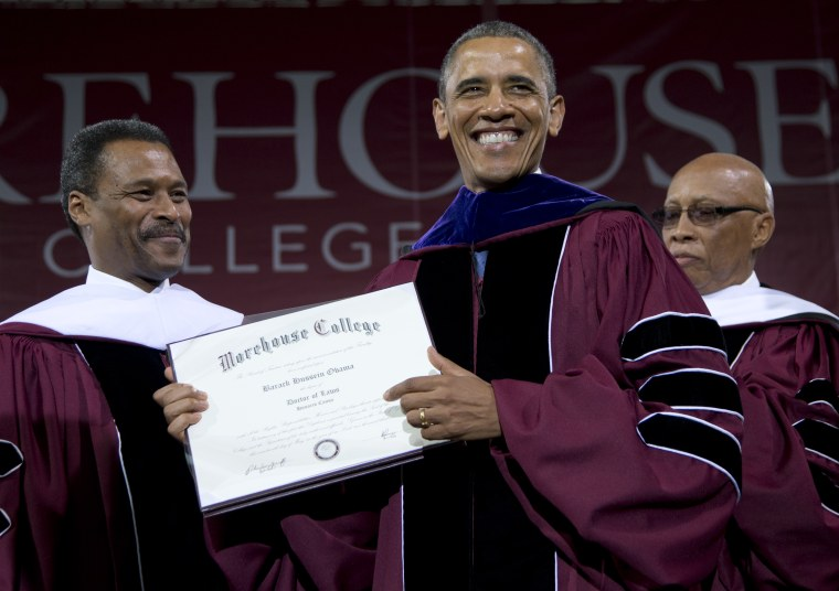 Morehouse College President John Silvanus Wilson Jr. stands left and Robert Davidson, Chair of the Board of Trustees, right, as President Barack Obama holds his honorary a doctorate of laws degree during the Morehouse College 129th Commencement...