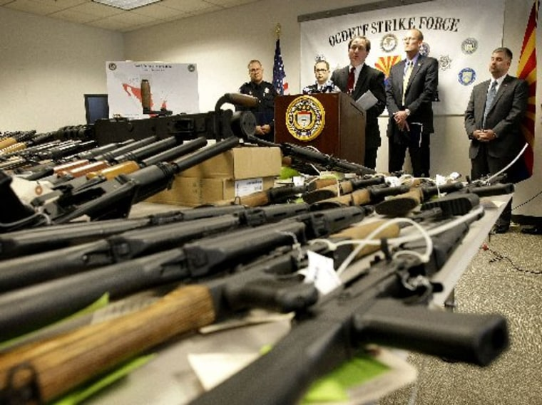 File Photo: United States Attorney for Arizona Dennis Burke speaks behind a cache of seized weapons Tuesday, Jan 25, 2011 in Phoenix. A grand jury has indicted 20 people on firearms charges for allegedly participating in a ring that bought more than...