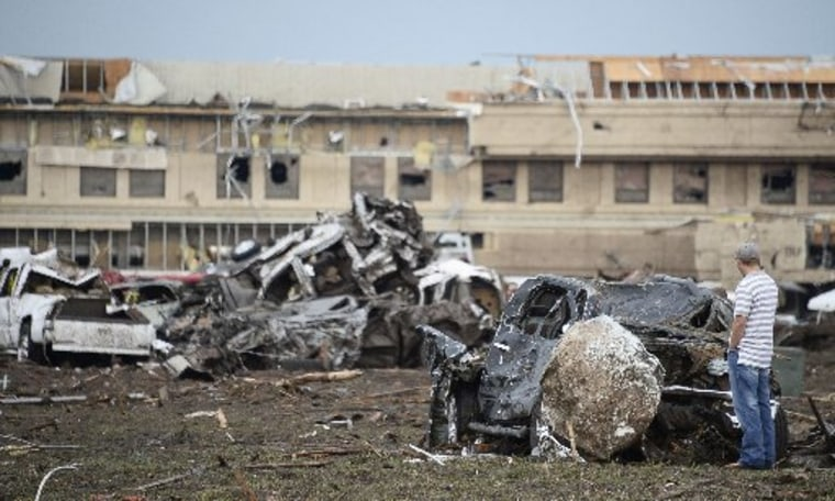 A man looks at a boulder that hit a car after a tornado struck Moore, Oklahoma, May 20, 2013. A 2-mile-wide (3-km-wide) tornado tore through the Oklahoma City suburb of Moore on Monday, killing at least 51 people while destroying entire tracts of homes...