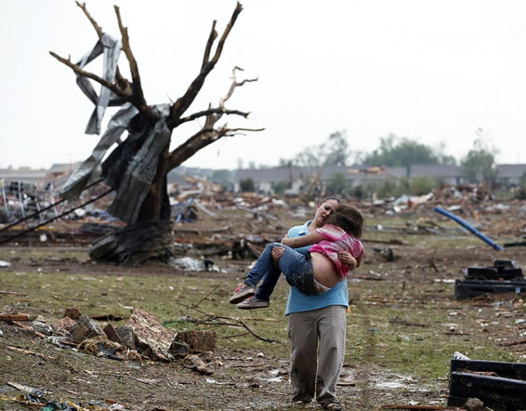 A woman carries a child through a field near the collapsed Plaza Towers Elementary School in Moore, Okla., Monday, May 20, 2013. A tornado as much as a mile wide with winds up to 200 mph roared through the Oklahoma City suburbs Monday, landing a direct...