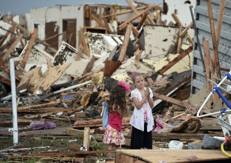 Two girls stand in rubble after a tornado struck Moore, Okla., May 20, 2013. A tornado tore through the Oklahoma City suburb of Moore on Monday, killing dozens while destroying entire tracts of homes, piling cars atop one another, and trapping school...