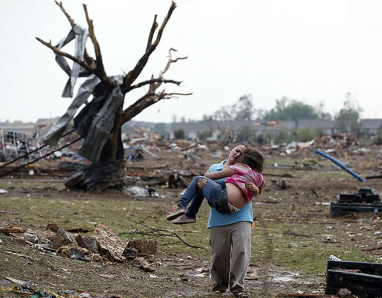 A woman carries a child through a field near the collapsed Plaza Towers Elementary School in Moore, Okla., Monday, May 20, 2013.  A tornado as much as a mile wide with winds up to 200 mph roared through the Oklahoma City suburbs Monday, flattening...