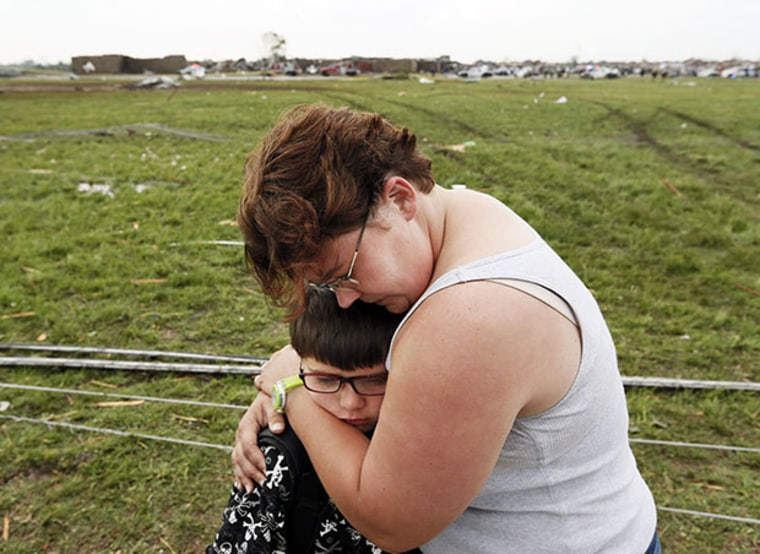 Rebekah Stuck hugs her son, Aiden Stuck, 7, after she found him in front of the destroyed Briarwood Elementary after a tornado struck south Oklahoma City and Moore, Okla., Monday, May 20, 2013. Aiden Stuck was inside the school when it was hit. (AP...