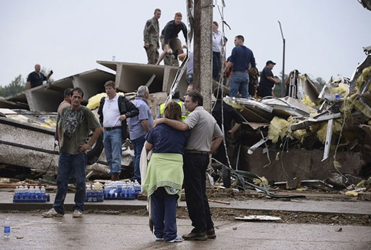Residents and rescuers look over the damage after a tornado struck Moore, Oklahoma, May 20, 2013. A huge tornado with winds of up to 200 miles per hour (320 kph) devastated the Oklahoma City suburb of Moore on Monday, ripping up at least two elementary...