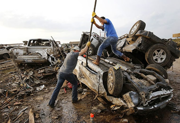 Two men attempt  to pry open a door on this car to check for victims in a business parking lot west of I-35 south of 4th Street in Moore, on May 20, 2013. (AP Photo/The Oklahoman, Jim Beckel)