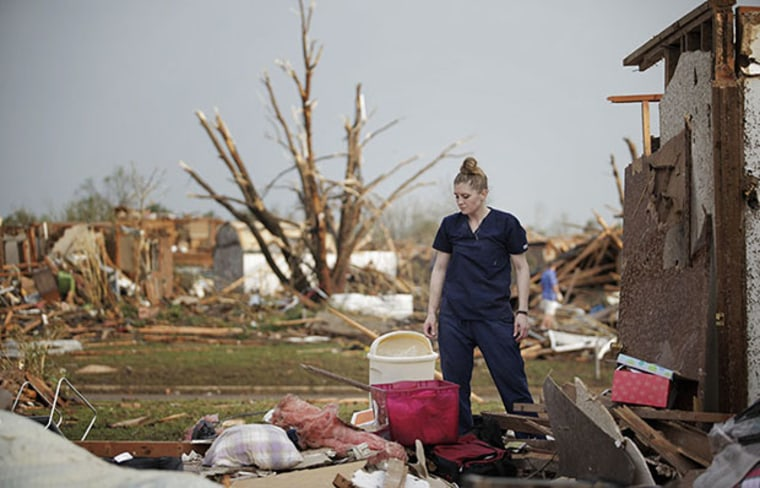 MOORE, OK- MAY 20:  Dana Ulepich looks at the debris from her house destroyed by a powerful tornado ripped through the area on May 20, 2013 in Moore, Oklahoma. The tornado, reported to be at least EF4 strength and two miles wide, touched down in the...
