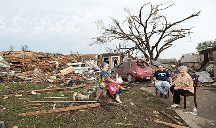 MOORE, OK - MAY 20:  (L - R) Yvonne Barragar, Joe Marshall and Barbara Garcia sit in front of Barragar's destroyed house after a powerful tornado ripped through the area on May 20, 2013 in Moore, Oklahoma. The tornado, reported to be at least EF4...