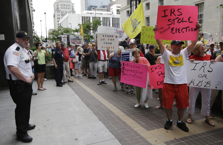 A federal officer watches as tea party activists demonstrate outside the John Weld Peck Federal Building, Tuesday, May 21, 2013, in Cincinnati. The building houses the main offices for the Internal Revenue Service in the city and is tied to the...
