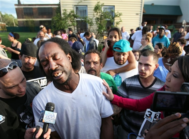 Charles Ramsey talks to media as people congratulate him on helping some women get out of a home in the 2200 block of Seymour Ave on May 6, 2013. (Scott Shaw / The Plain Dealer)