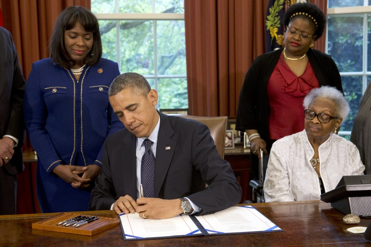 President Barack Obama signs a bill designating the Congressional Gold Medal commemorating the lives of the four young girls killed in the 16th Street Baptist Church Bombing of 1963, Friday, May 24, 2013, in the Oval Office of the White House. Standing...