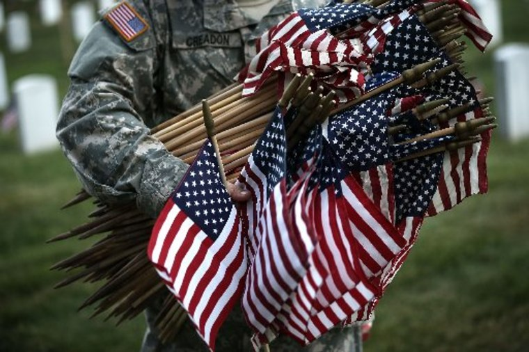 """A member of the Fife and Drum Corps of the 3rd U.S. Infantry Regiment, """"The Old Guard,"""" participate in a """"Flags-In"""" ceremony May 23, 2013 at Arlington National Cemetery in Arlington, Virginia. A small American flag was placed one foot in front of more..."""