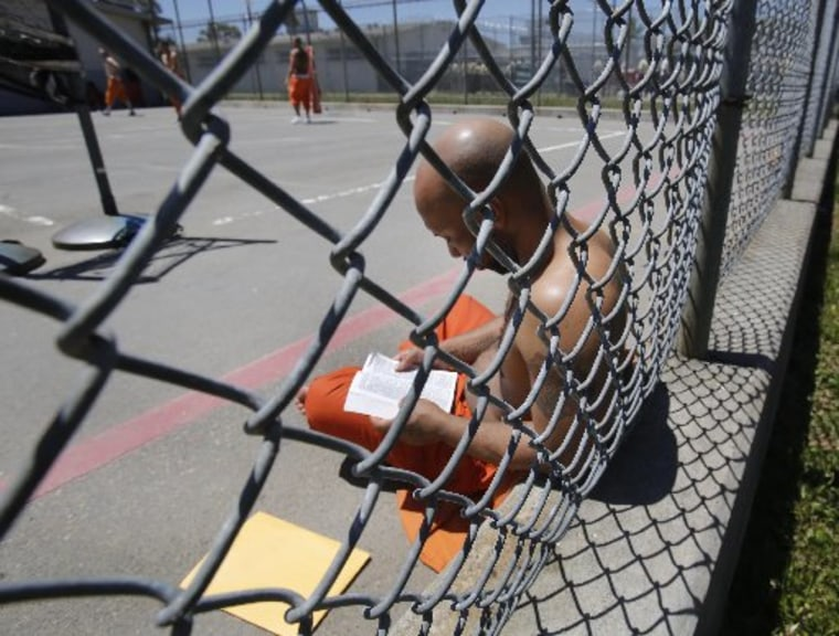 Inmate Curtis Colvard Sr. reads a Bible in the exercise yard of Sacramento County's Rio Cosumnes Correctional Center in Elk Grove, Calif., Thursday, May 30, 2013.  A report by the California Little Hoover Commission  says Gov. Jerry Brown's prison...