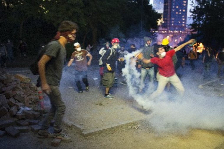 ISTANBUL, TURKEY - Protesters throw a tear gas back at Turkish police during clashes near Turkish prime minister Recep Tayyip Erdogan office, between Taksim and Besiktas on June 3, 2013 in Istanbul, Turkey. (Photo by Uriel Sinai/Getty Images)