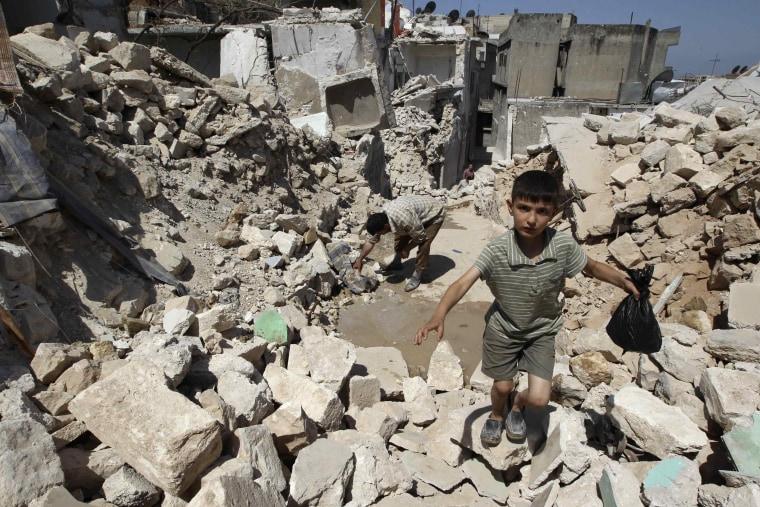 A boy walks on the rubble of buildings damaged by what activists said were missiles fired by Syrian Air Force fighter jets loyal to President Bashar al-Assad in Salqin city, Idlib governate, May 28, 2013. (Photo by Muzaffar Salman/Reuters)