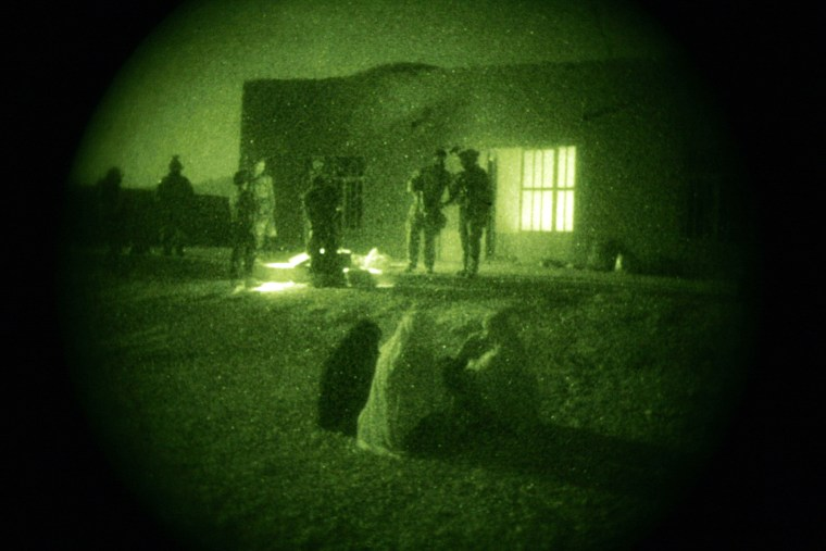 FILE - In this Oct. 28, 2009 file photo taken with a night vision scope, Afghan women and their children wait as U.S. Special Operations forces and Afghan National Army soldiers search their home during a joint operation targeting insurgents operating...