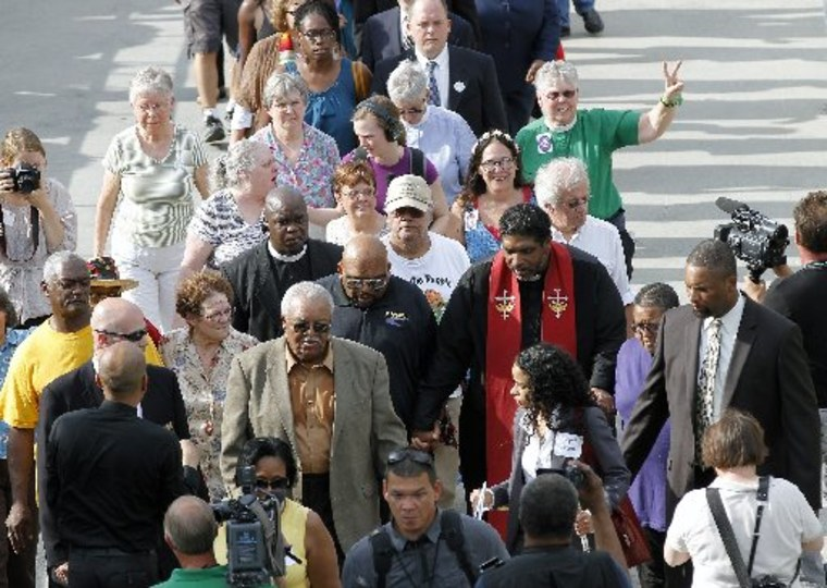 The Rev. William Barber, right center, with red sash, leads a group into the Legislative Building as the Monday protests are held at the General Assembly in Raleigh, NC on Monday, June 3, 2013. (Photo by: Chris Seward/AP Photo/The News & Observer)