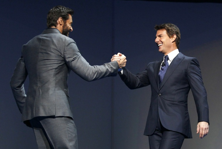 Actor Hugh Jackman (L) welcomes actor Tom Cruise to the stage as Jackman hosts the annual shareholders meeting for Walmart in Fayetteville, Arkansas June 7, 2013. (REUTERS/Rick Wilking)