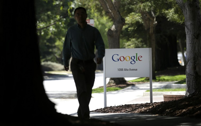 A man walks past a Google sign in Mountain View, Calif., Friday, June 7, 2013. Google CEO Larry Page is denying reports linking the Internet search company to a secret government program that has provided the National Security Agency access to email...
